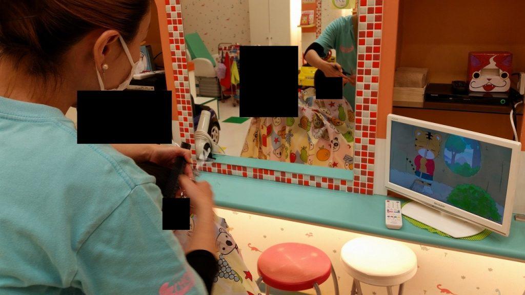 素早く赤ちゃんの髪を切るチョッキンズの店員